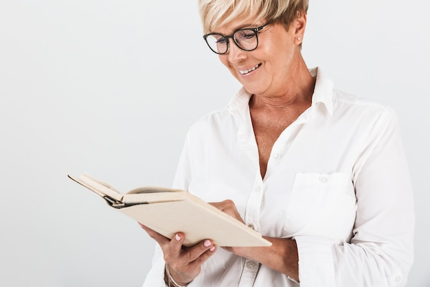 Портрет радостной взрослой женщины в очках, читающей книгу, изолированную над белой стеной в студии