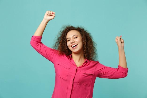 スタジオの青いターコイズブルーの壁の背景に分離された勝者のような拳を食いしばっているピンクのカジュアルな服を着た楽しいアフリカの女の子の肖像画。人々の誠実な感情、ライフスタイルのコンセプト。コピースペースをモックアップします。