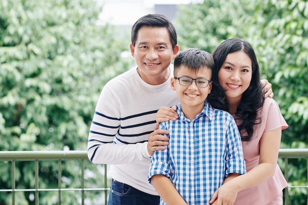 離れたバルコニーに立っているときに笑っているうれしそうなアジアの母、父とそのプレティーンの子供の肖像画