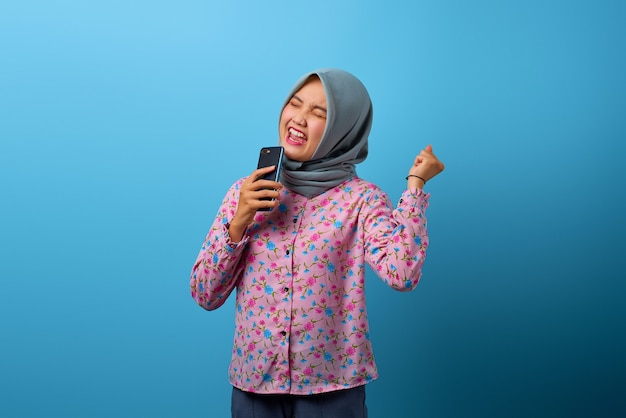 うれしそうなアジアの女性の肖像画は、スマートフォンでダンスの動きと歌で手を上げました