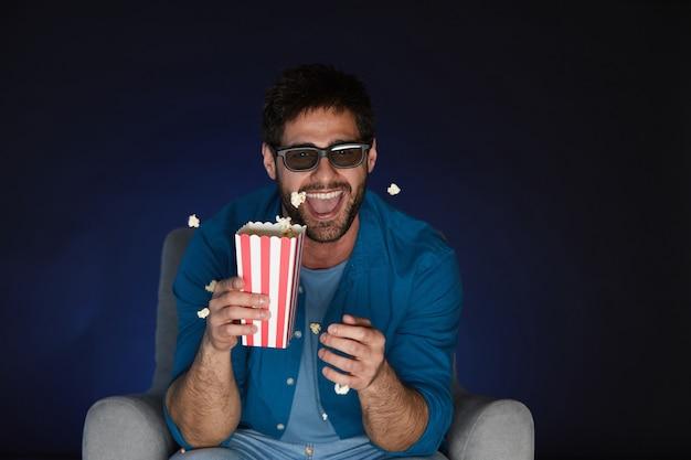 暗闇の中で自宅で映画を見ながらポップコーンを食べる3dメガネをかけてうれしそうなひげを生やした男の肖像画