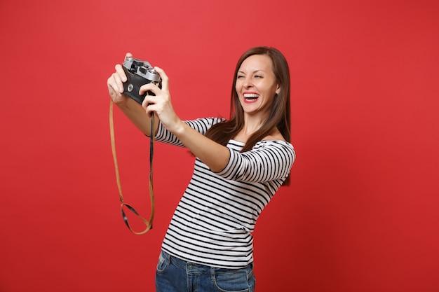 真っ赤な壁の背景に分離されたレトロなビンテージ写真カメラでselfie撮影をしているうれしそうな美しい若い女性の肖像画。人々の誠実な感情、ライフスタイルのコンセプト。コピースペースをモックアップします。