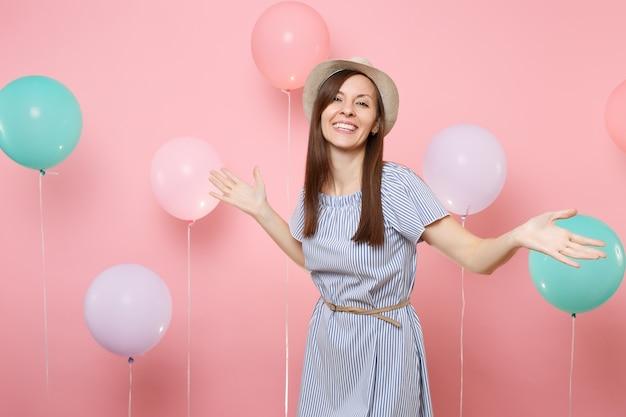 짚으로 만든 여름 모자와 파란색 드레스를 입은 즐거운 아름다운 젊은 여성의 초상화는 화려한 공기 풍선과 함께 파스텔 핑크색 배경에 손을 펼치고 있습니다. 생일 휴일 파티 사람들은 진심 어린 감정.