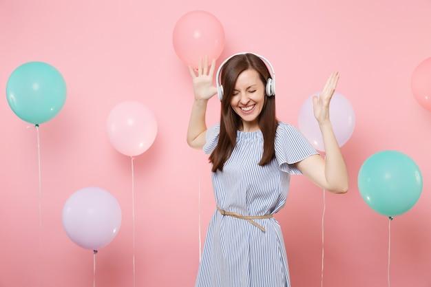 Портрет радостной красивой молодой женщины с наушниками в голубом платье, слушая музыку, распространяя руки на розовом фоне с красочными воздушными шарами. день рождения, праздник, у людей искренние эмоции.