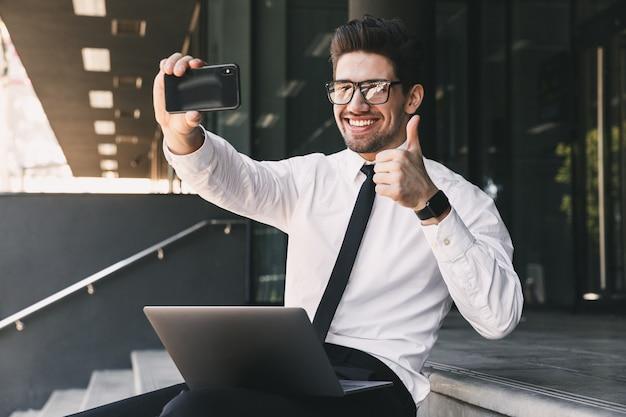 ノートパソコンでガラスの建物の外に座って、スマートフォンで自分撮り写真を撮るフォーマルなスーツに身を包んだうれしそうなビジネスマンの肖像画