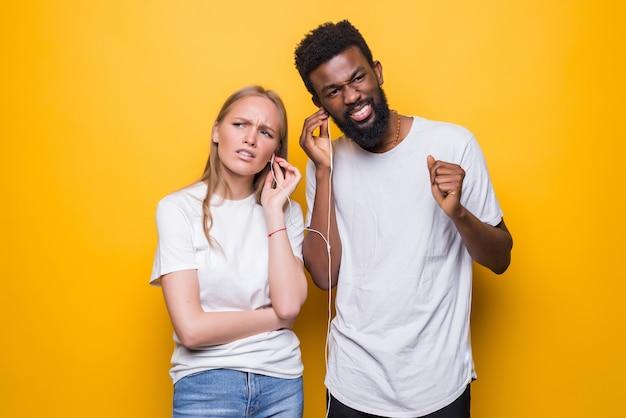 Портрет радостной пары, поющей, используя смартфон и наушники вместе, изолированные на желтой стене