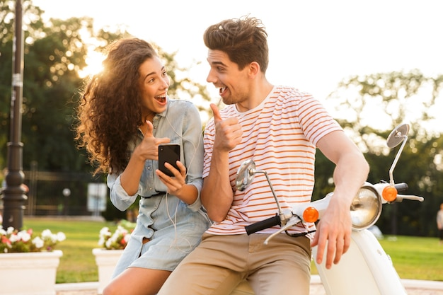 즐거운 부부의 초상화, 도시 거리에 스쿠터에 함께 앉아 스마트 폰을 사용하는 이어폰을 착용