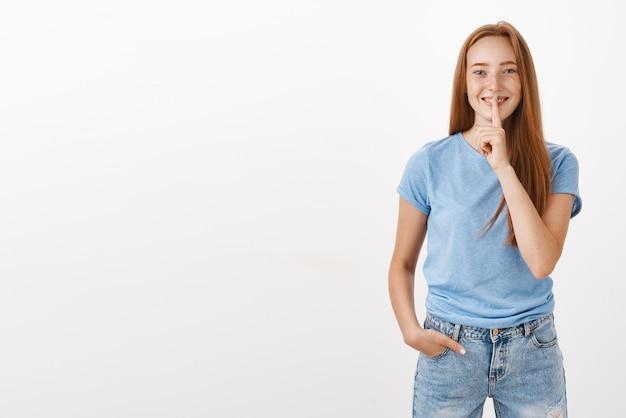 Портрет радостной, милой и беззаботной рыжей женщины в синей футболке и джинсах, показывающей жест прикрытия рта указательным пальцем