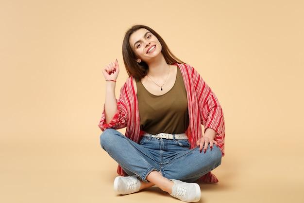 スタジオでパステルベージュの壁の背景に分離されたカメラを探して座っているカジュアルな服を着た楽しいかわいい笑顔の若い女性の肖像画。人々の誠実な感情、ライフスタイルのコンセプト。コピースペースをモックアップします。