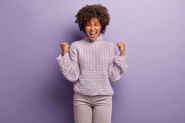 Портрет радостной темнокожей модели триумфально сжимает кулаки, обрадовало выражение лица, выражает счастье после одержанной победы, носит фиолетовую одежду, активно жестикулирует в помещении