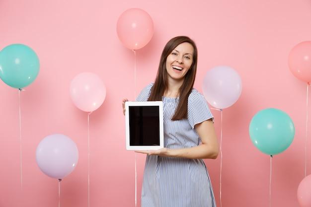 カラフルな気球とパステルピンクの背景に空白の空の画面でタブレットpcコンピューターを保持している青いドレスを着てうれしそうな魅力的な若い女性の肖像画。誕生日の休日のパーティーのコンセプト。
