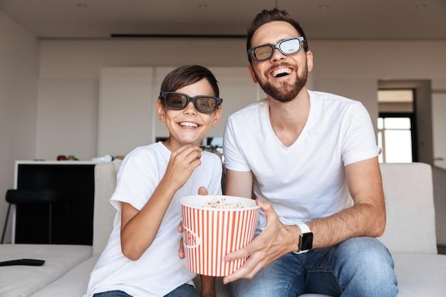 Портрет радостного отца и сына в 3d-очках, едящих попкорн и улыбающихся, сидя на диване в помещении и смотря фильм