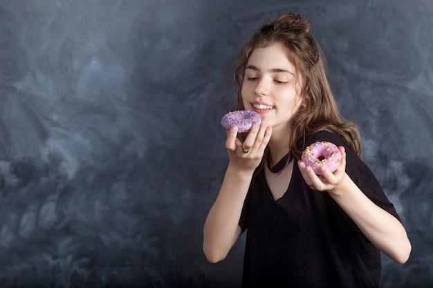 黒い壁にドーナツとうれしそうな女の子の肖像画。幸せな女の子は新鮮なドーナツを持って、それらを見ます。良い気分、ダイエットのコンセプト。