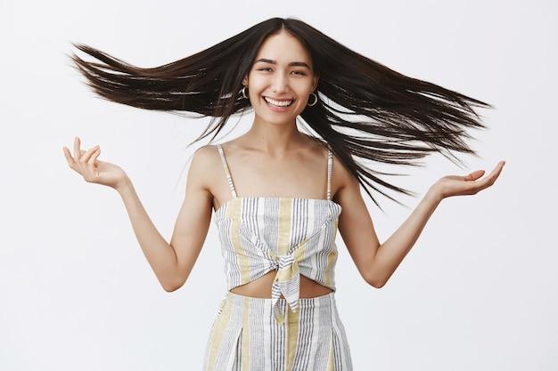 新しいスタイリッシュなヘアスタイルを作り、手を上げ、風に浮かぶ髪を振って、広く笑った後の楽しいかっこいい女性モデルの肖像画