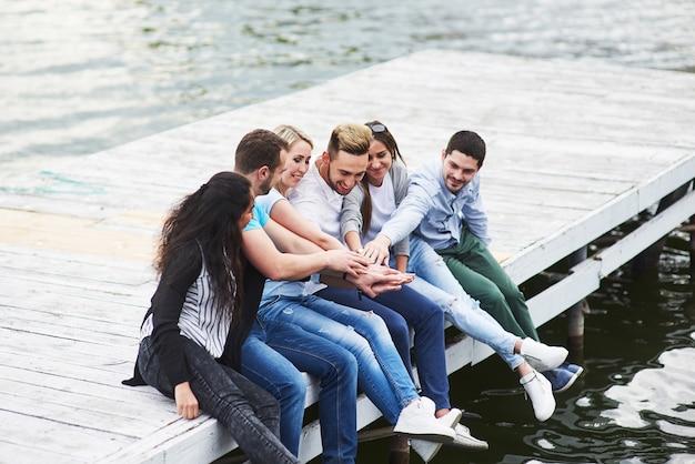 桟橋の端に座っている若い人たちの楽しいグループの肖像画