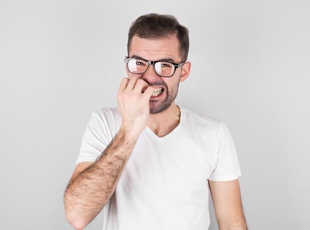 즐거운 잘 생긴 수염 난 남자의 초상화는 치아를 움켜 쥐고, 눈을 깜박이며, 회색 배경 위에 손톱을 물다.