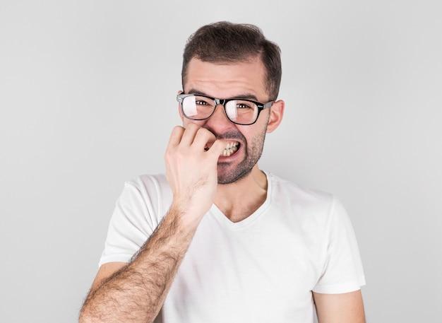 즐거운 잘 생긴 수염 난 남자의 초상화는 이빨을 움켜 쥐고, 눈을 깜박이며, 회색 벽에 손톱을 물다.