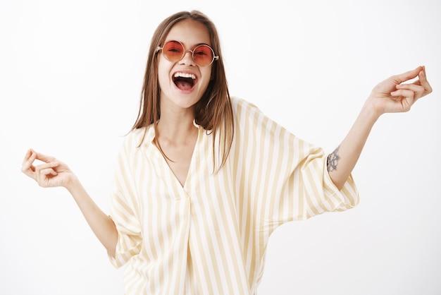 Портрет радостной, счастливой и веселой беззаботной стильной женщины в модных красных солнцезащитных очках и желтой полосатой блузке танцует и поет песню вслух с широкой улыбкой и раздвинутыми руками