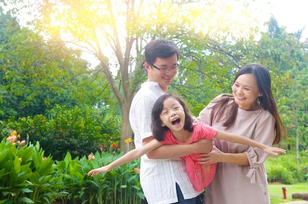 여름 일몰 동안 야외 공원에서 함께 연주 즐거운 행복 아시아 가족의 초상화.