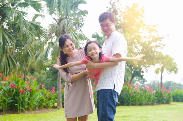 여름 일몰 동안 야외 공원에서 함께 연주 즐거운 행복 아시아 가족의 초상화. 프리미엄 사진