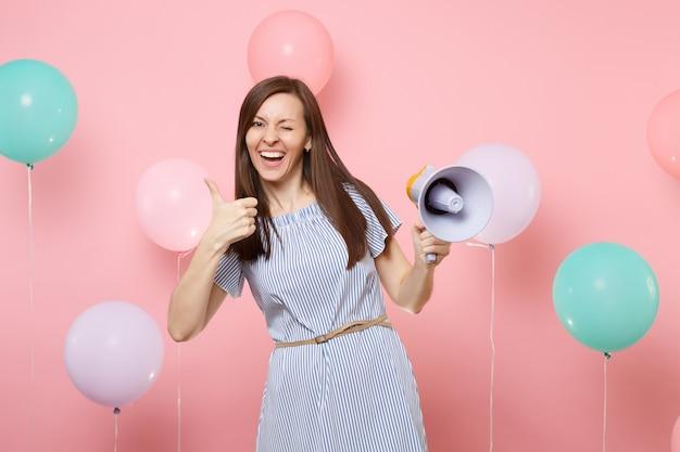 Портрет радостной счастливой милой молодой женщины, носящей голубое платье, моргающего, держа мегафон, показывая большой палец вверх на розовом фоне с красочными воздушными шарами. день рождения праздник у людей искренние эмоции.