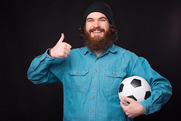 Портрет радостного бородатого хипстера, показывающего большой палец вверх и держащего футбольный мяч