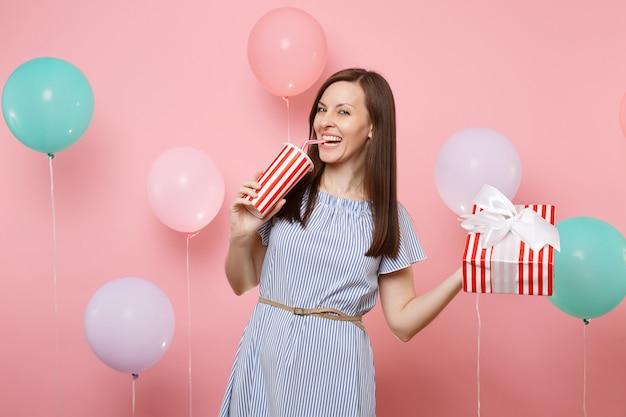파란 드레스를 입은 즐거운 웃고 있는 여성의 초상화는 선물이 있는 빨간색 상자를 들고 파스텔 핑크색 배경에 다채로운 공기 풍선이 있는 플라스틱 컵에서 소다나 콜라를 마시는 것입니다. 생일 휴일 파티.