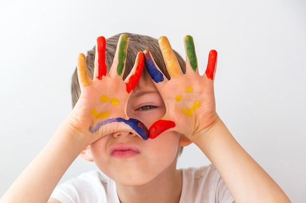 Портрет радостного маленького мальчика с красочными раскрашенными руками