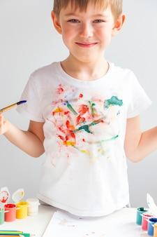 Портрет радостного маленького мальчика с красочной раскрашенной футболкой