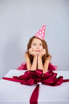 Портрет радостной маленькой девочки в розовом платье и шляпе положил локти на большую подарочную коробку
