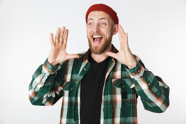 Портрет радостного человека в шляпе и клетчатой рубашке кричит или зовет, стоя изолированным на белом фоне
