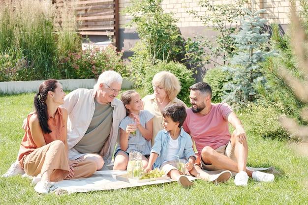 ピクニックをしている晴れた夏の日に裏庭の芝生に座って楽しい多世代家族の肖像画