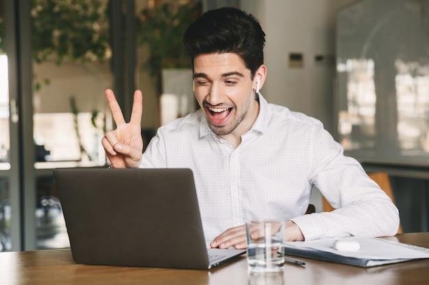 Портрет радостного офисного мужчины 30-х годов в белой рубашке, смеющегося и показывающего знак мира на ноутбуке, во время видеоконференции или звонка с помощью наушников bluetooth
