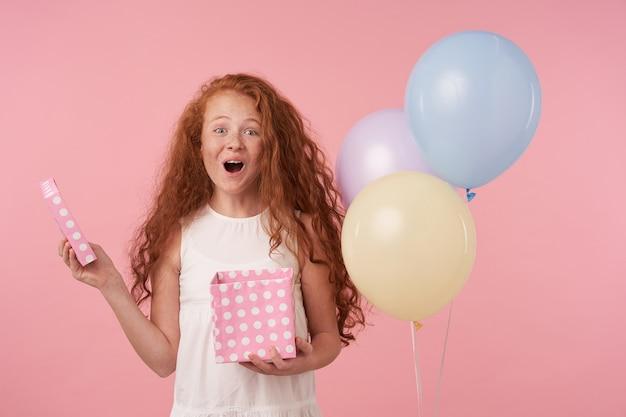 エレガントな服を着て、手にプレゼントボックスを持って、それを開梱することに興奮している、ピンクの背景の上にカメラで喜んで見ている長い巻き毛の楽しい赤毛の女の子の肖像画