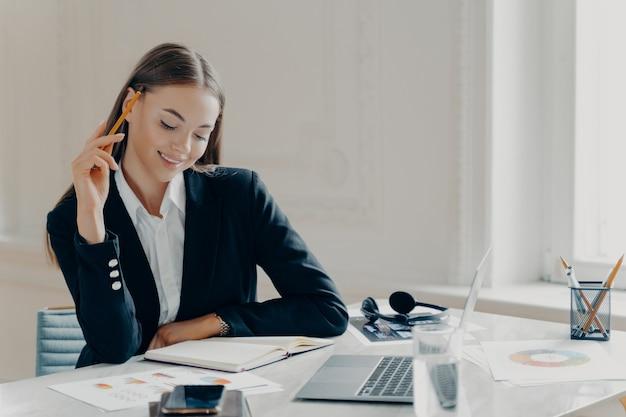 Портрет радостной, улыбающейся молодой кавказской деловой женщины в черном формальном костюме, сидящей за большим белым столом с записной книжкой и ноутбуком с легким минималистичным фоном.