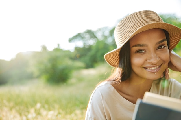 Портрет радостной женщины с пирсингом в губе и соломенной шляпе, читающей книгу, сидя на траве в зеленом парке