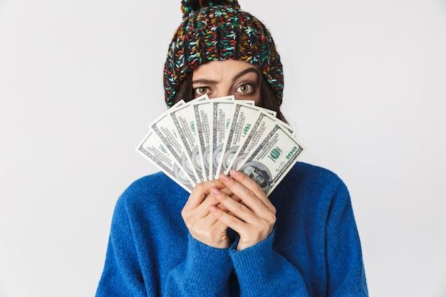 Портрет радостной женщины в зимней шапке, держащей веер долларовых денег стоя, изолированной на белом