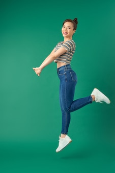 緑の上を空中でジャンプするうれしそうな若いアジアの女性の肖像画。
