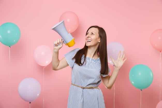 Портрет радостной молодой attaractive женщины, носящей голубое платье, держащей мегафон, разводя руками на розовом фоне с красочными воздушными шарами. праздник дня рождения, концепция искренних эмоций людей.