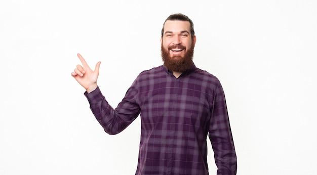 Портрет радостного молодого бородатого мужчины, указывающего на угол на белом фоне