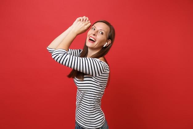줄무늬 옷을 입은 즐거운 어린 소녀의 초상화는 무선 이어폰이 빨간 배경에 격리된 음악을 들으며 상승하는 손을 춤추고 있습니다. 사람들은 진심 어린 감정 라이프 스타일 개념입니다. 복사 공간을 비웃습니다.