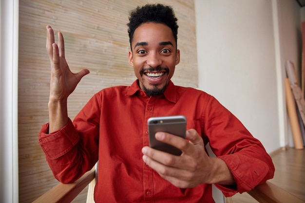 Портрет радостного молодого симпатичного короткошерстного темнокожего мужчины с бородой, поднимающего руку, весело глядя с широкой улыбкой, позирующего в домашнем интерьере