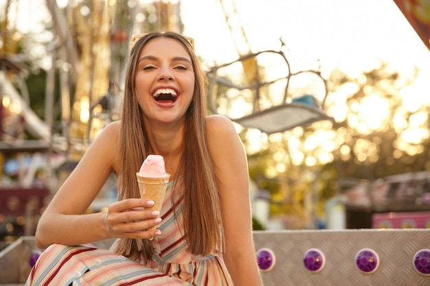 アトラクションの公園の上で屋外でポーズをとって、大きな口を開けて笑い、アイスクリームコーンを手に持って、頭にサングラスをかけた楽しい若い素敵な女性の肖像画