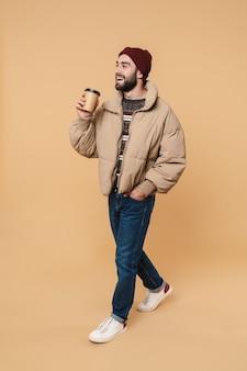Портрет радостного молодого человека в зимней куртке и шляпе, улыбающегося, держа чашку кофе, изолированную на бежевом