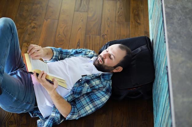 그의 거실 바닥에 앉아있는 동안 책을 읽고 즐거운 젊은 남자의 초상화. 책을 들고 읽는 학생.