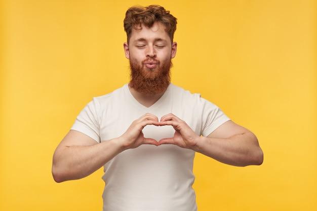Портрет радостного молодого человека, одетого в пустую футболку, показывает сердце руками, любовный жест на желтом