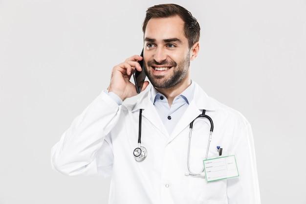 Портрет радостного молодого врача со стетоскопом, работающего в клинике и говорящего по мобильному телефону, изолированного над белой стеной