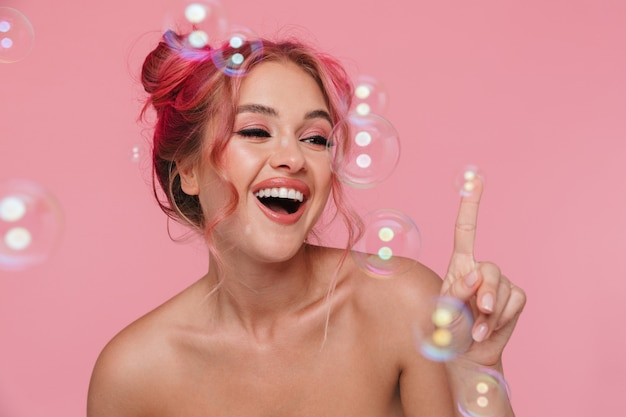 シャボン玉で笑顔とポーズをとってうれしそうな若い上半身裸の女性の肖像画