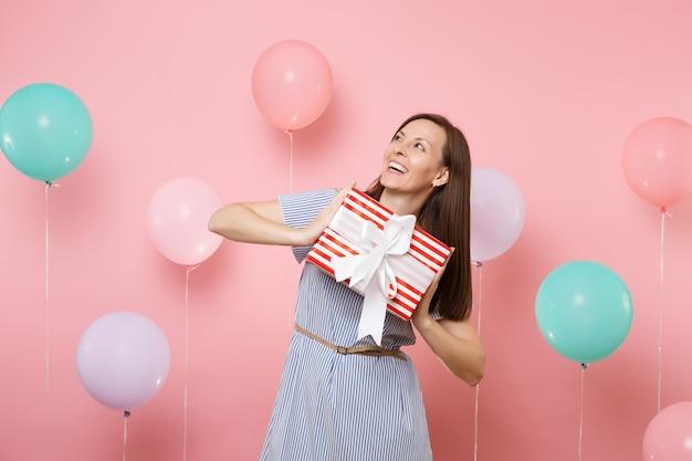 カラフルな気球とピンクの背景にプレゼントプレゼントと赤い箱を保持しているコピースペースを見上げる青いドレスのうれしそうな若い女性の肖像画。誕生日ホリデーパーティー、人々は心からの感情。