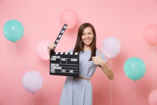 Портрет радостной молодой женщины в голубом платье, показывающей большой палец вверх, удерживает классический черный фильм, делая с 'хлопушкой' на розовом фоне с красочными воздушными шарами. день рождения, праздник, у людей искренние эмоции.